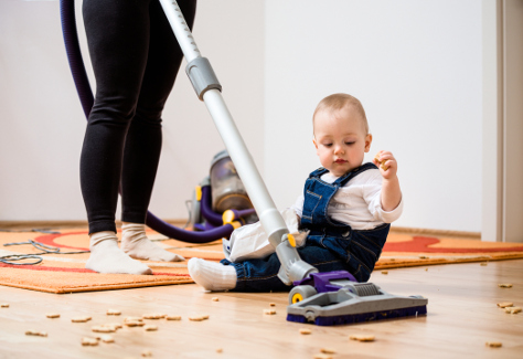 Mum hoovering while baby on the floor