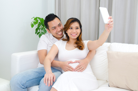 Expectant couple taking selfie