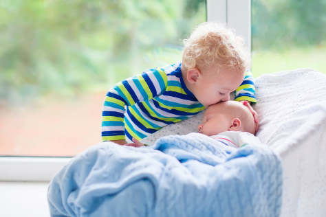 Age gap boy kissing baby brother