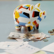 An image of a piggy bank and allowance money on a table
